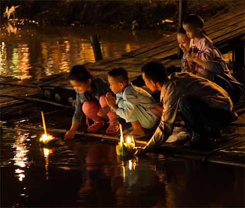Une famille thaie depose un krathong dans la rivière a Chiang Mai